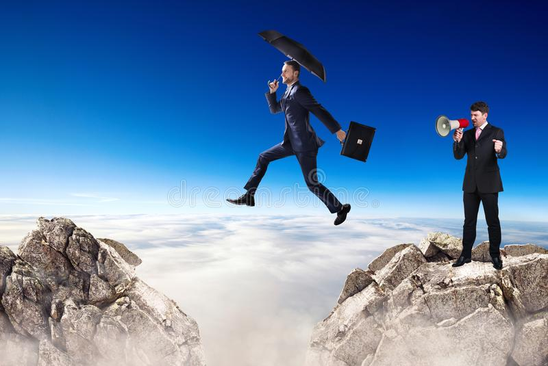 Businessman jumping over a cliff and collegue is cheering with bullhorn. royalty free stock photo