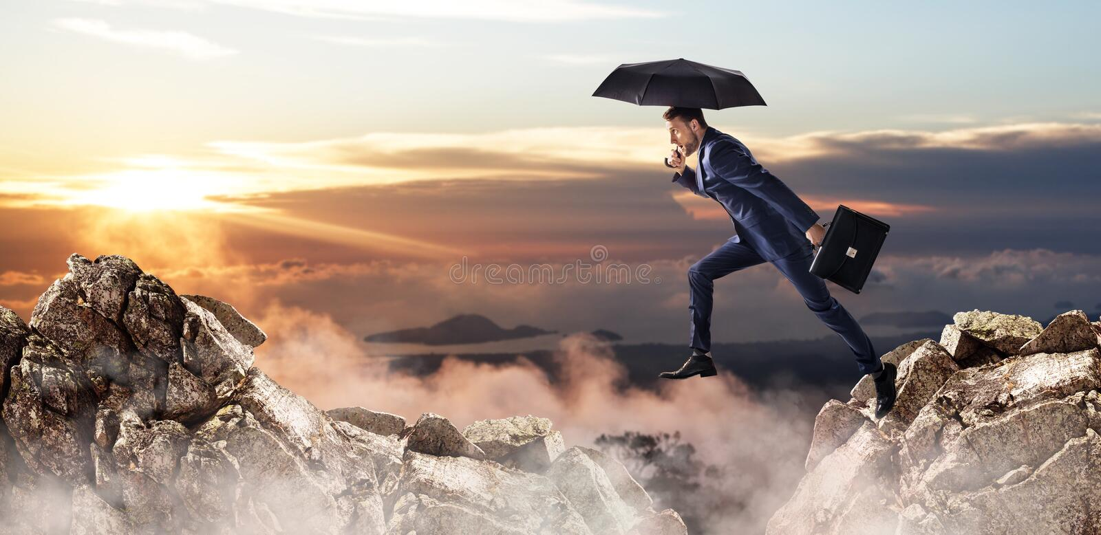 Businessman jumping over a cliff with umbrella and briefcase. royalty free stock image