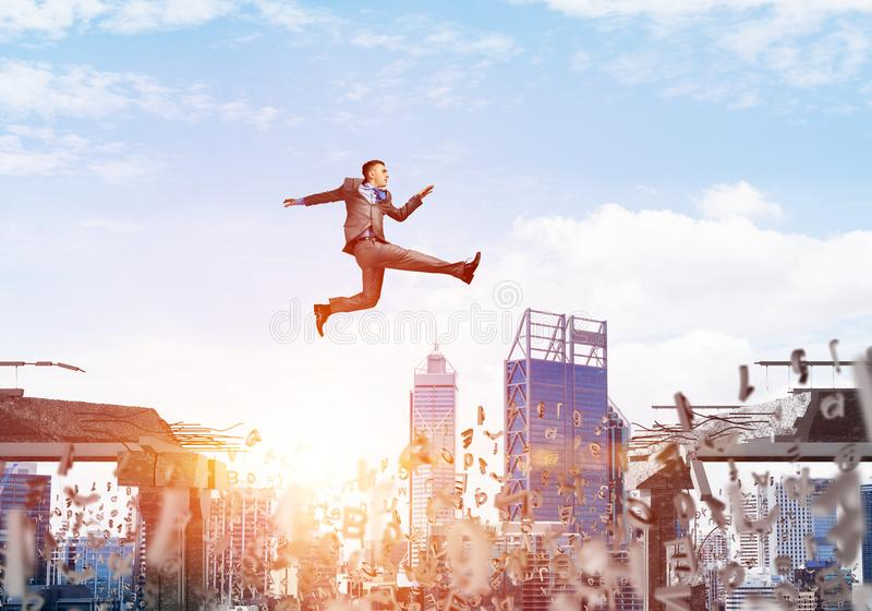 Problem and difficulties overcoming concept. Businessman jumping over gap with flying letters in concrete bridge as symbol of overcoming challenges. Cityscape stock photos