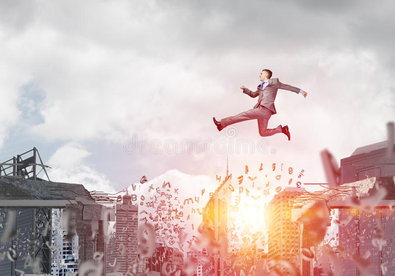 Problem and difficulties overcoming concept. Businessman jumping over gap with flying letters in concrete bridge as symbol of overcoming challenges. Cityscape stock image