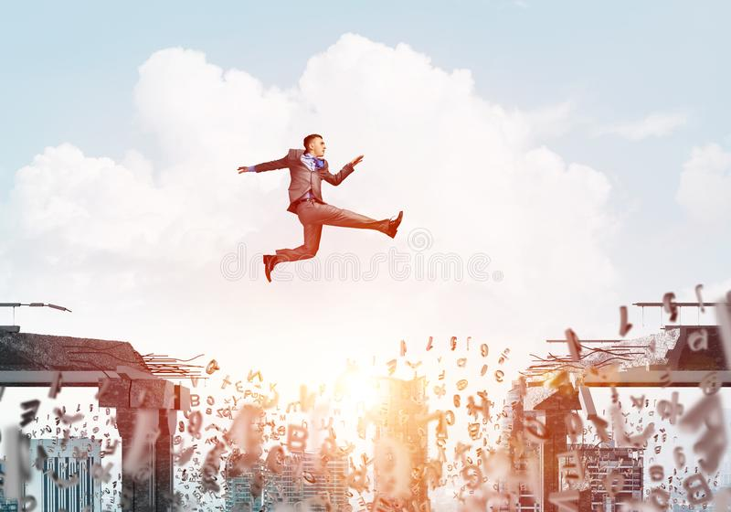Problem and difficulties overcoming concept. Businessman jumping over gap with flying letters in concrete bridge as symbol of overcoming challenges. Cityscape royalty free stock image