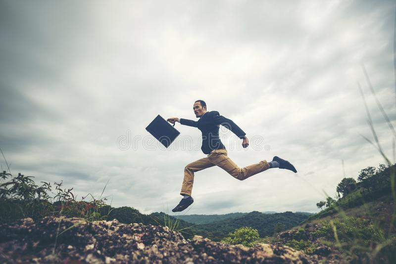 Businessman jumping over the mountain, business worker concept royalty free stock photos