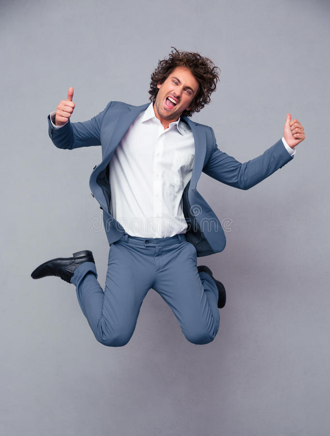 Businessman jumping and showing thumbs up. Portrait of a funny businessman jumping and showing thumbs up isolated on a white background stock images