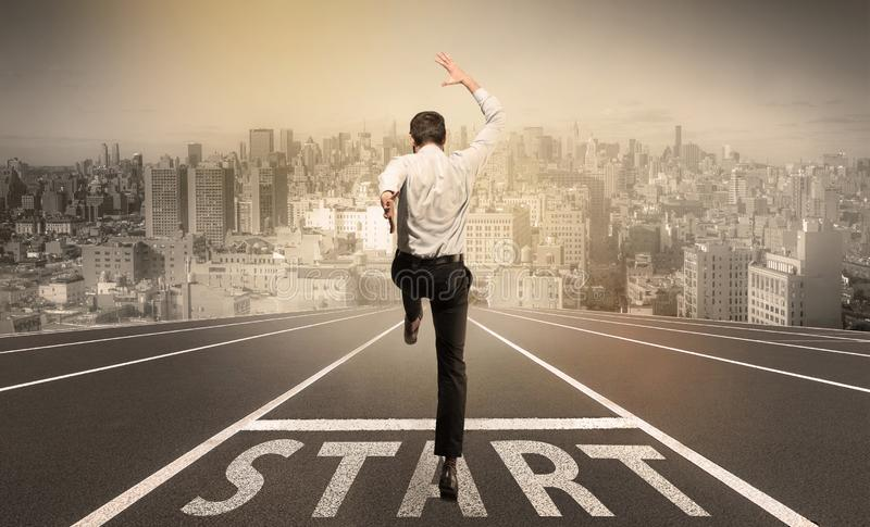 Businessman jumping on a starting grid with cityscape on the background stock photos