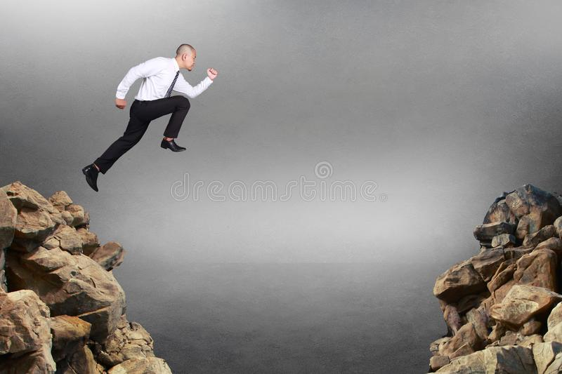 Businessman Jumping Trough Obstacle Gap. Composite image. Businessman running jumping trough obstacle gap, business risk concept royalty free stock photography