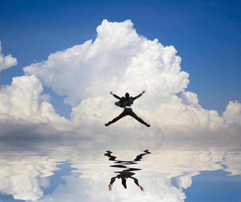 Businessman jumping on the water and cloud stock images