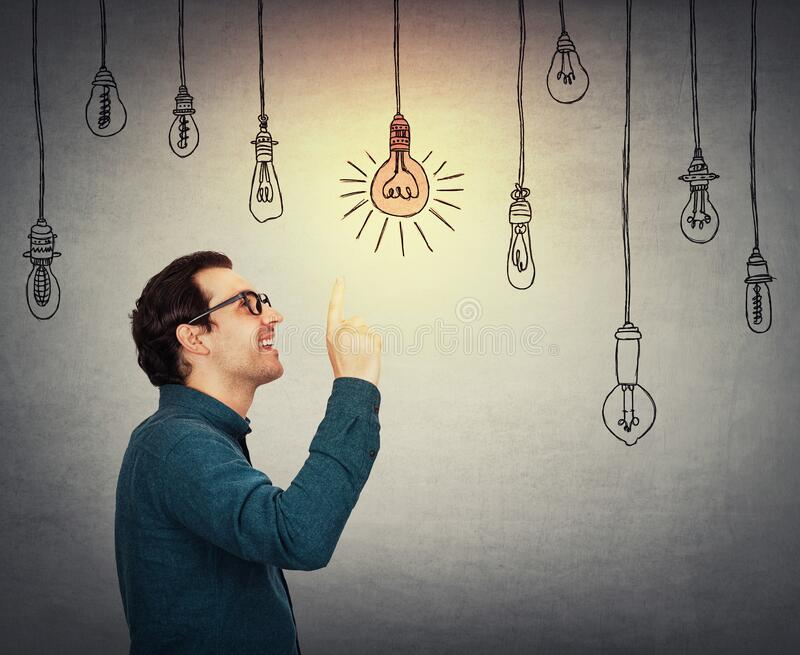 Businessman keeps index finger pointed up, eureka gesture, choosing a hanging glowing light bulb from others switched off. royalty free stock photo
