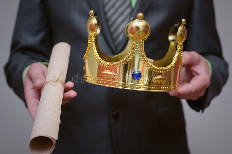 Golden crown in the hands. Businessman king holding in hands a gold crown and royal decree scroll special offer document stock image