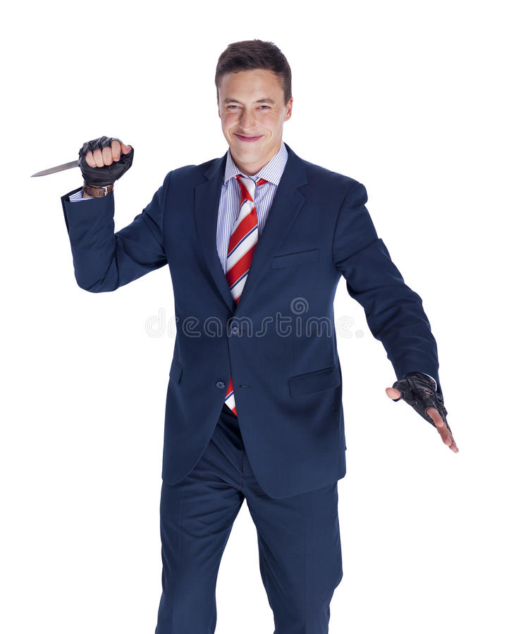 Businessman with a knife. Smiling businessman with a knife ready to stab royalty free stock photos