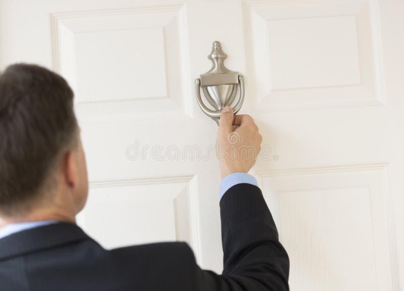 Businessman Knocking Door Knocker. Rear view of mature businessman knocking door knocker royalty free stock photography