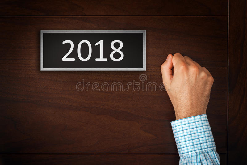 Businessman knocking on door with number 2018. Happy New Year conceptual image, celebration at the door royalty free stock images