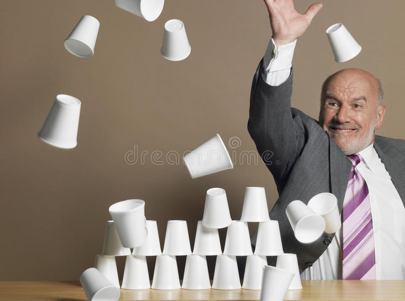 Businessman Knocking Down Pyramid Of Cups. Middle aged businessman knocking down pyramid of plastic cups against brown background royalty free stock photo