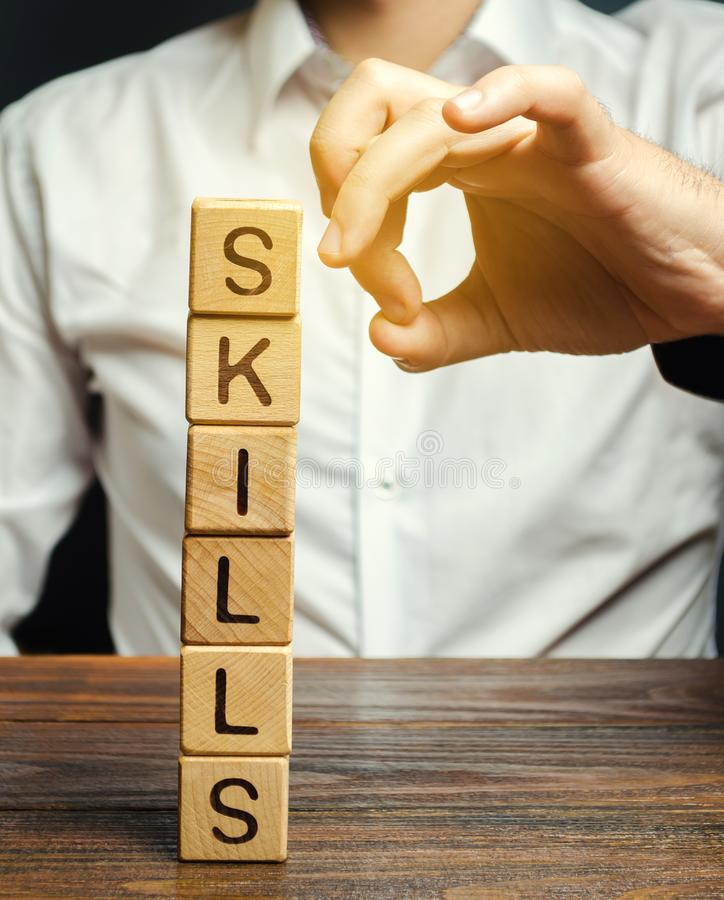 Businessman knocks down wooden blocks with the word Skills. The concept of the loss of skills. Suppression of talents. Business. Planning, financial modeling royalty free stock photography