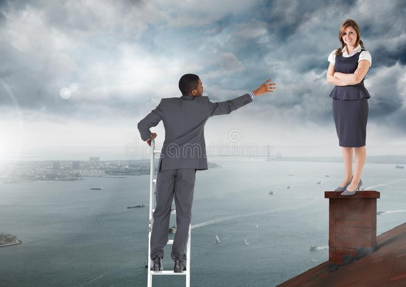 Businessman on ladder reaching for help to Businesswoman standing on Roof with chimney and cloudy ci royalty free stock image