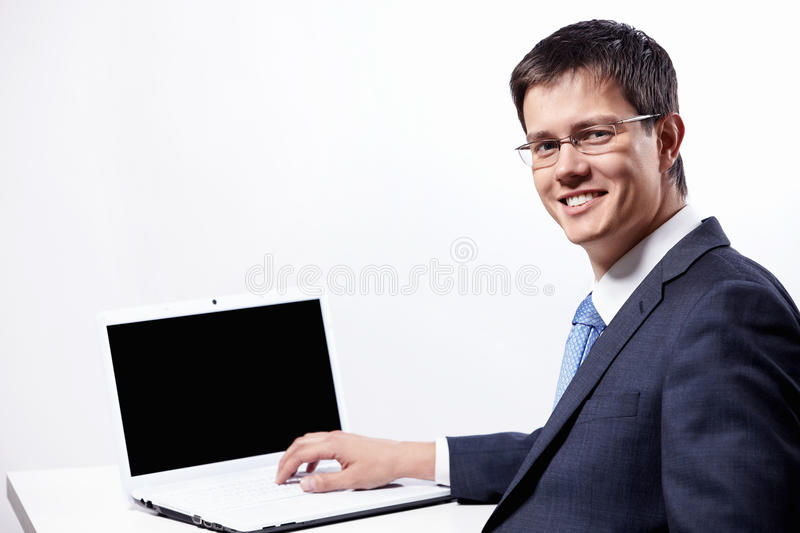 Businessman with laptop. Mature businessman in glasses with a laptop stock photography