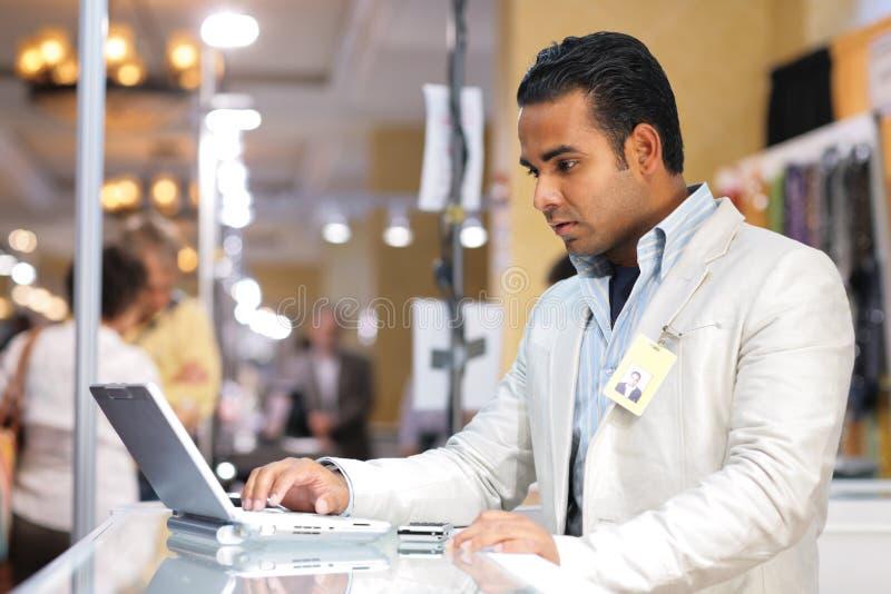 Businessman laptop. Young indian businessman using laptop computer at trade show