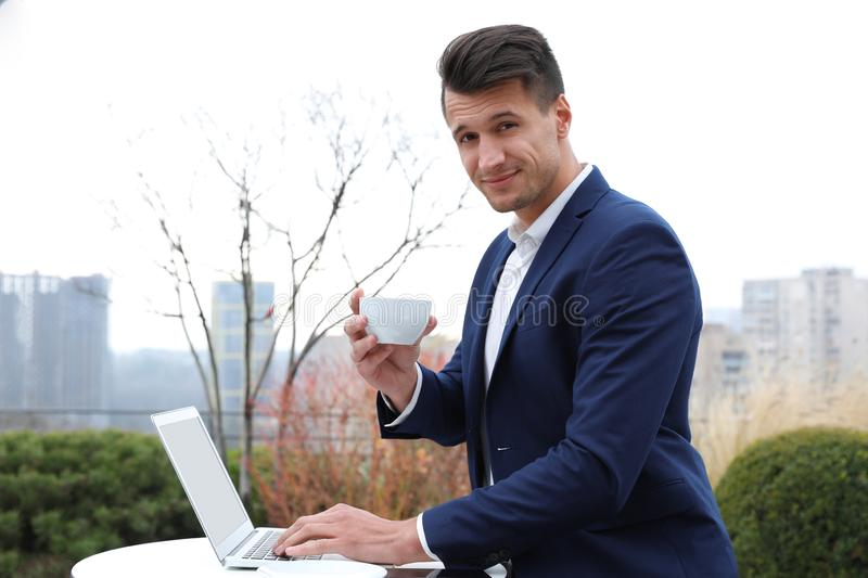 Businessman with laptop and coffee in cafe. Corporate blog. Businessman with laptop and coffee in outdoor cafe. Corporate blog royalty free stock photos