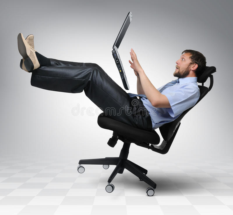 Businessman with laptop falls from an chair stock images