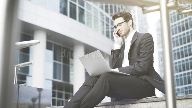 Businessman with a laptop having a call in the open-air. A young prospective business man in a black suit working in the open-air with a laptop having a call. A royalty free stock photography