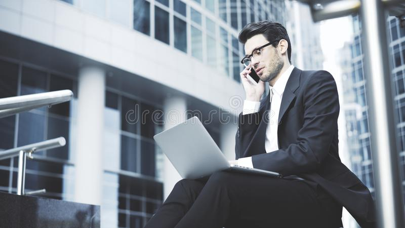 Businessman with a laptop having a call in the open-air. A young prospective business man in a black suit working in the open-air with a laptop having a call. A royalty free stock photos