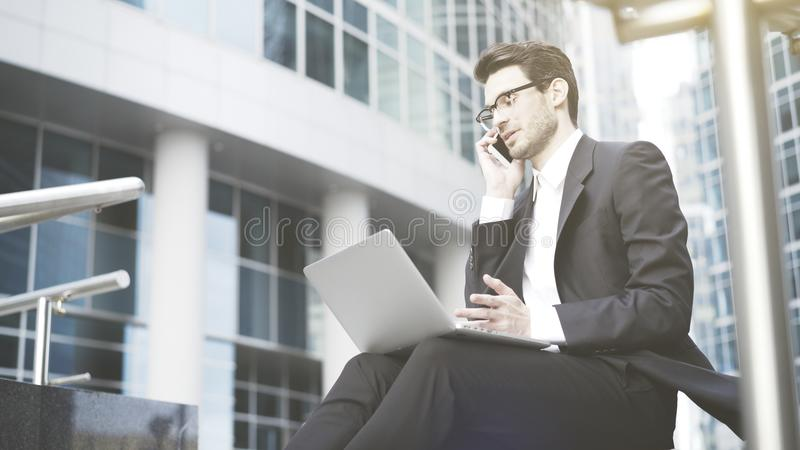 Businessman with a laptop having a call in the open-air. A young prospective business man in a black suit working in the open-air with a laptop having a call. A royalty free stock photo
