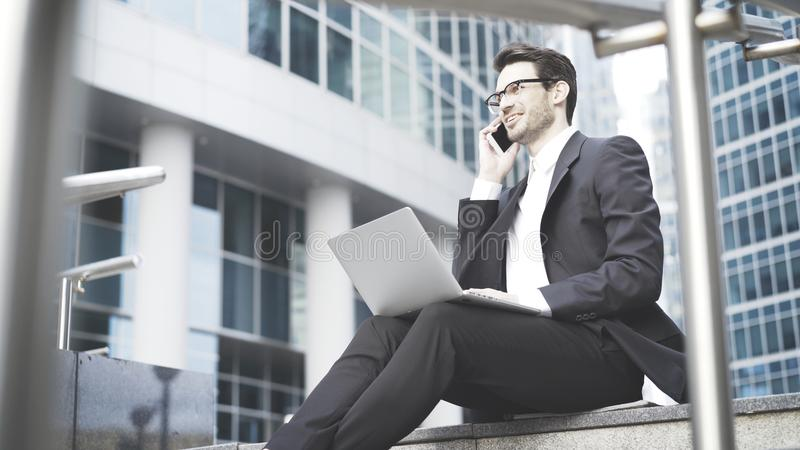 Businessman with a laptop having a call in the open-air. A young prospective business man in a black suit working in the open-air with a laptop having a call stock photos