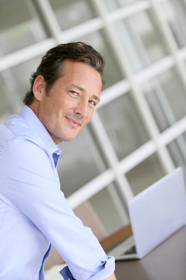 Businessman with a laptop in his office royalty free stock images
