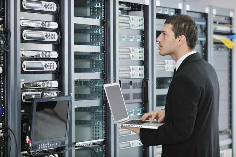 Businessman with laptop in network server room. Young engeneer business man with thin modern aluminium laptop in network server room
