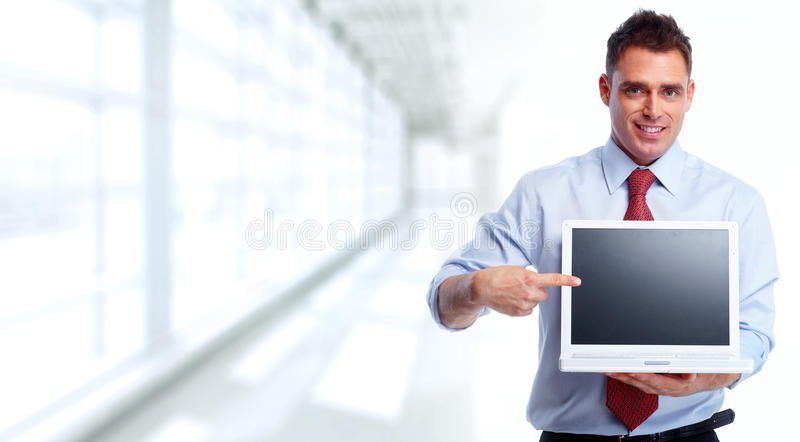 Businessman with laptop. Businessman presenting laptop computer screen over blue office background stock images