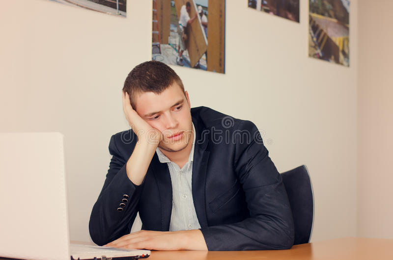 Businessman with Laptop Resting Head on Hand royalty free stock photos