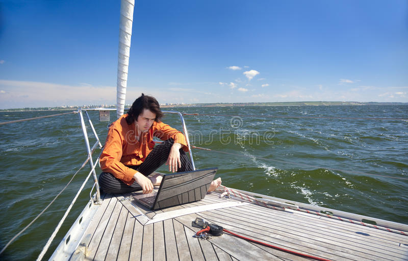 Businessman with laptop on sailboat stock images