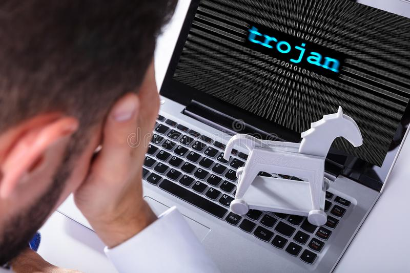 Businessman With Laptop Screen Showing Trojan Text. With Binary Digits stock photos