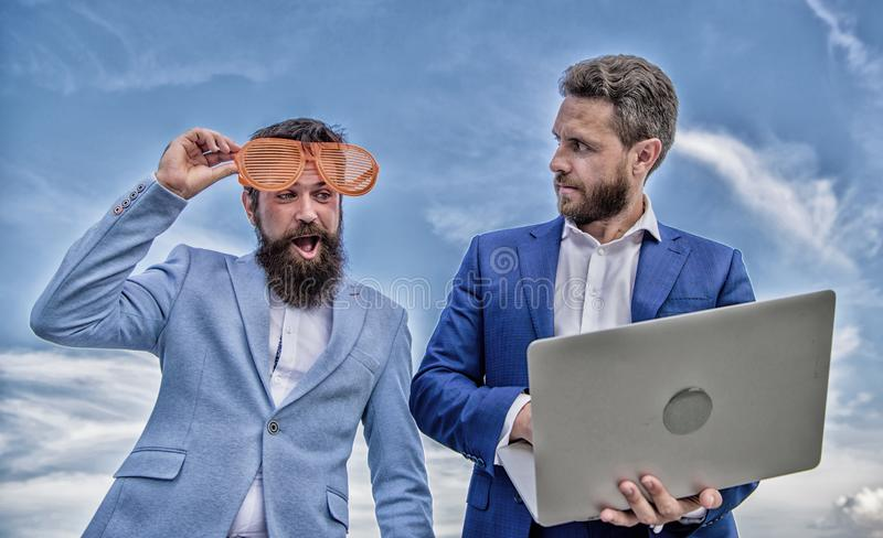 Businessman with laptop serious while business partner ridiculous glasses looks funny. How stop play entrepreneurship stock photography