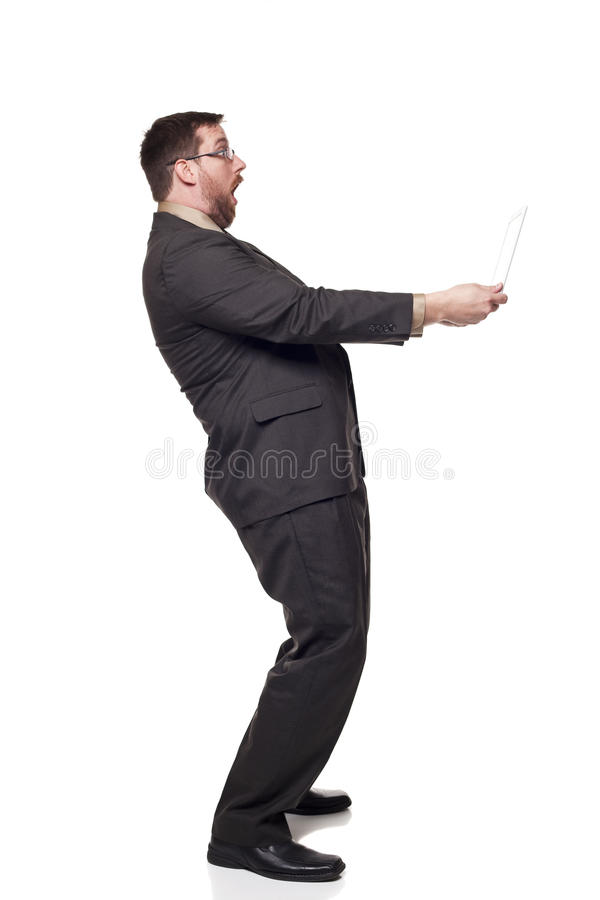 Businessman laptop shocked expression. Isolated full length studio shot of the side view of a businessman holding a laptop at arms length as if afraid of what is royalty free stock image