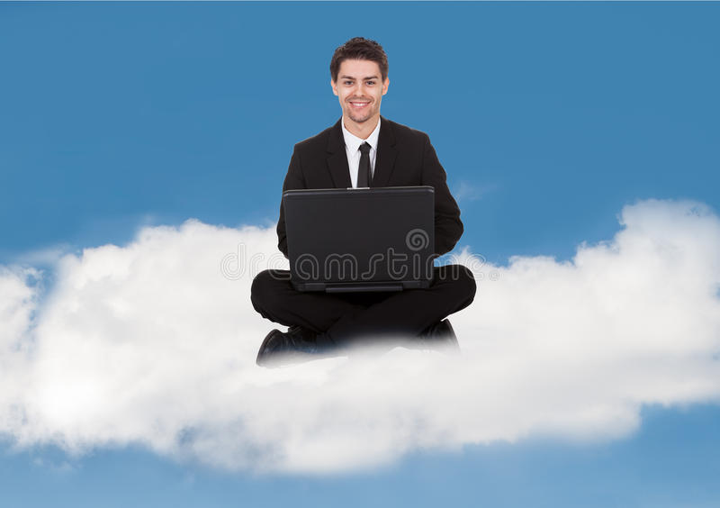Businessman With Laptop. Businessman sitting in yoga pose working on laptop on a cloud royalty free stock image