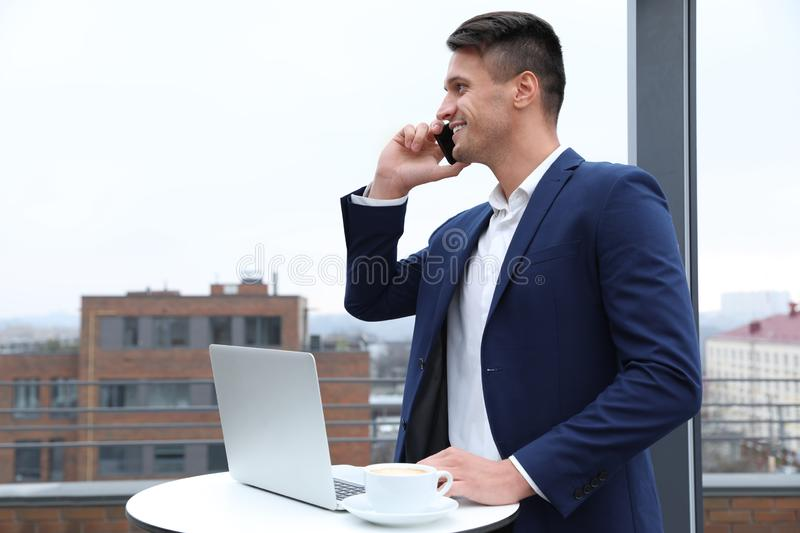 Businessman with laptop talking on phone in cafe. Corporate blog. Businessman with laptop talking on phone in outdoor cafe. Corporate blog royalty free stock photos