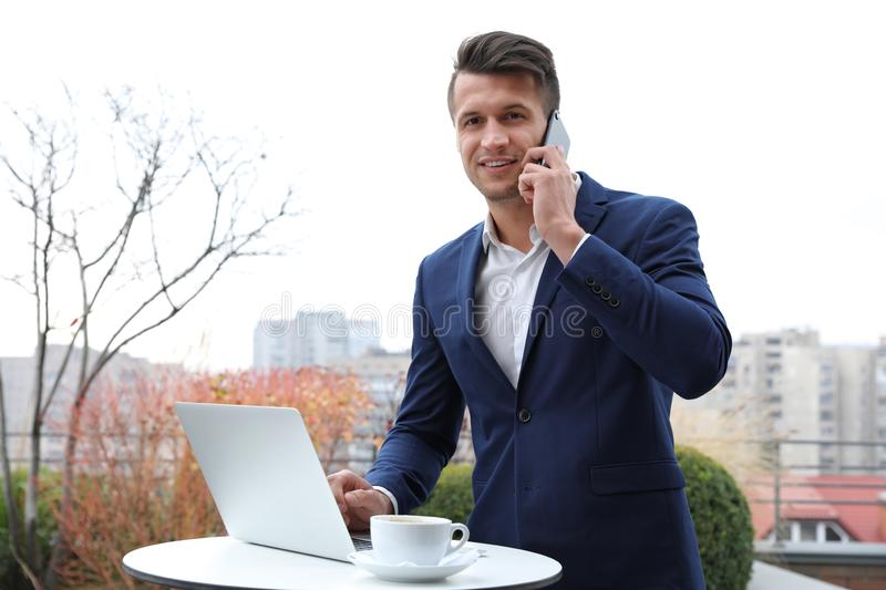 Businessman with laptop talking on phone in cafe. Corporate blog. Businessman with laptop talking on phone in outdoor cafe. Corporate blog royalty free stock photography