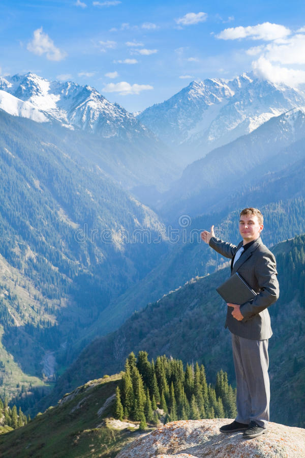 The businessman with laptop at the top of the mountain royalty free stock images