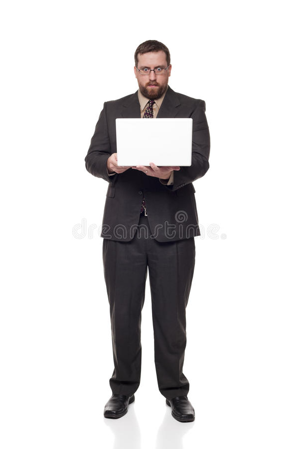 Businessman laptop wide eyed expression. Isolated full length studio shot of a businessman with a wide eyed expression looking at a laptop as if he can't believe stock photos