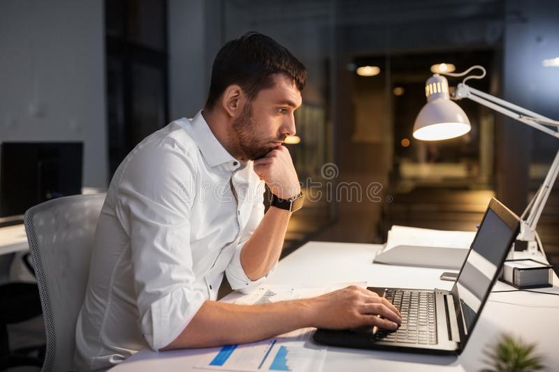Businessman with laptop working at night office stock photo