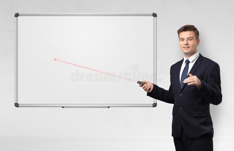 Businessman with laser pointer and copyspace white blackboard royalty free stock photo