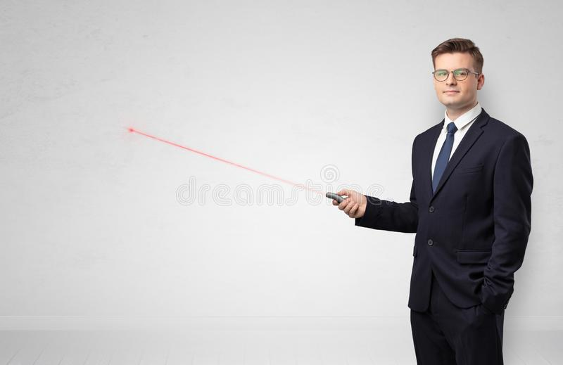 Businessman with laser pointer and copyspace white wall royalty free stock image