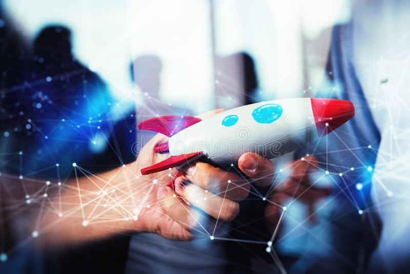 Businessman launches his startup company. Hand holding a toy rocket. double exposure with network effects. Wooden toy on background of people silhouettes royalty free stock image