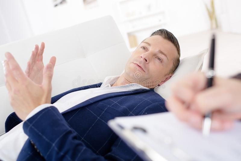 Businessman laying on couch talking to psychiatrist. Businessman laying on a couch talking to his psychiatrist royalty free stock photos