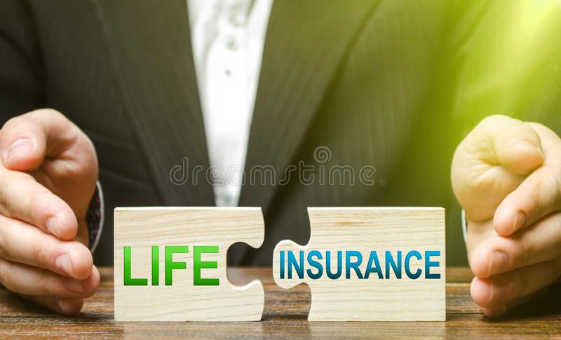 Businessman lays out puzzles with inscriptions life insurance. Medical service providing affordable medicine at the expense stock images