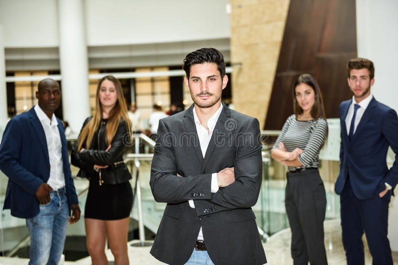 Businessman leader with arms crossed in working environment stock photography