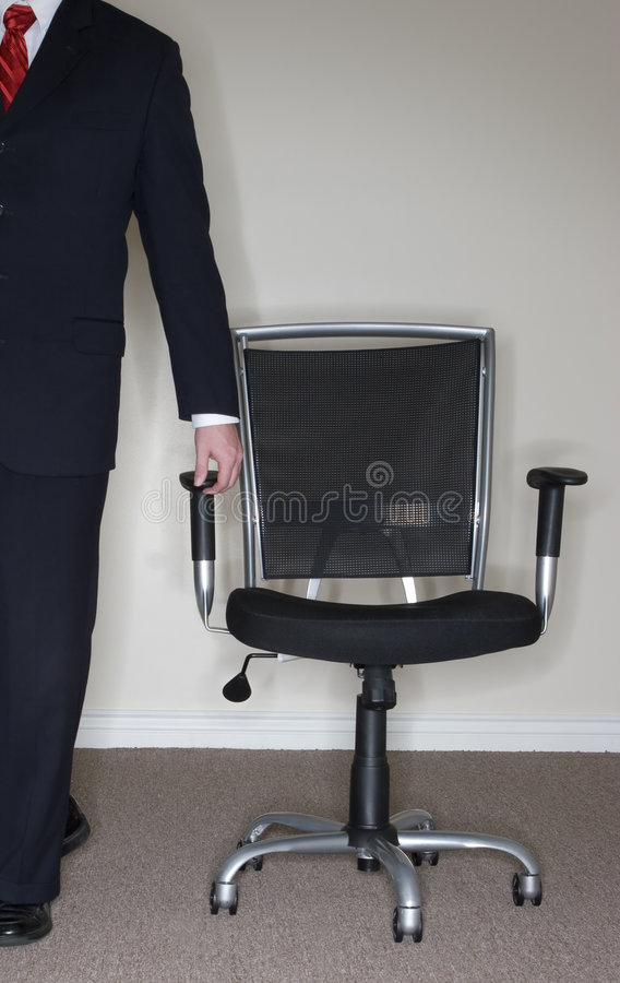 Businessman leading Chair;. Businessman wearing full suit grabs empty office chair stock photo
