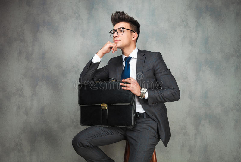 Businessman leaning his elbow against wall and looks away. Young businessman leaning his elbow against wall and looks away from the camera in studio royalty free stock images