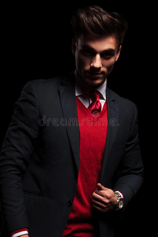 Businessman leaning his elbow against wall and looks away. Young businessman leaning his elbow against wall and looks away from the camera in studio stock photo