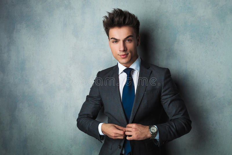 Businessman leaning his elbow against wall and looks away. Young businessman leaning his elbow against wall and looks away from the camera in studio stock images
